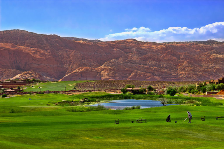 Green grass of golf course with red rocks and blue sky as backdrop