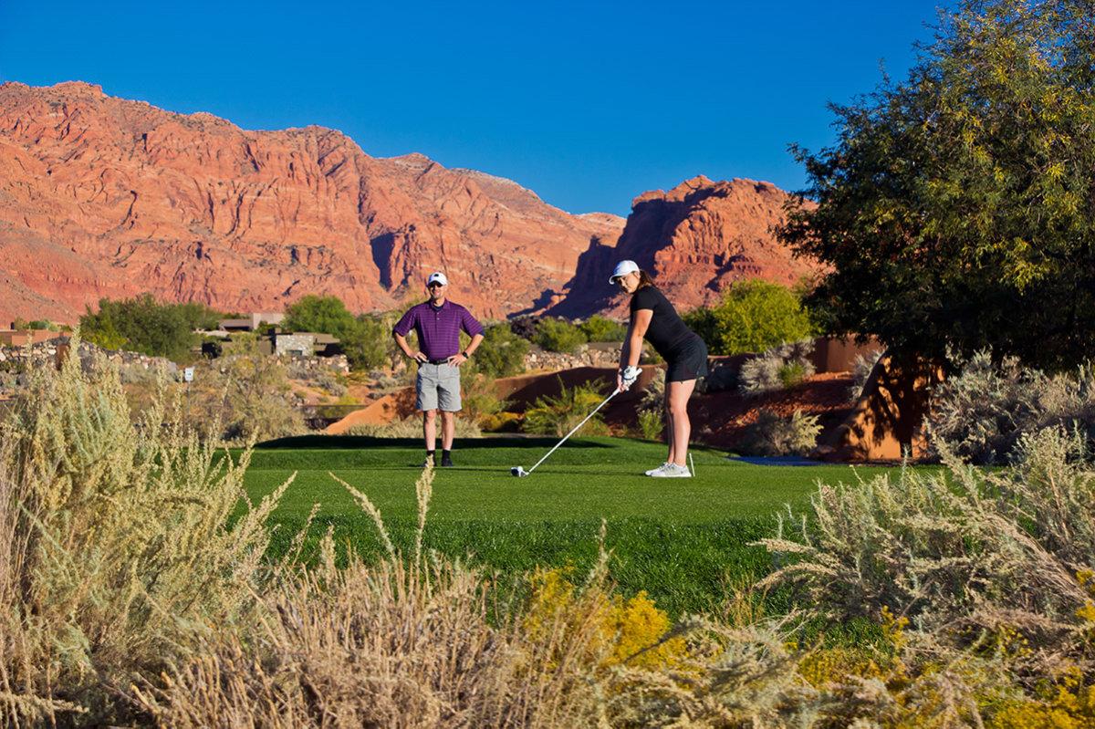 Couple golfing on desert course