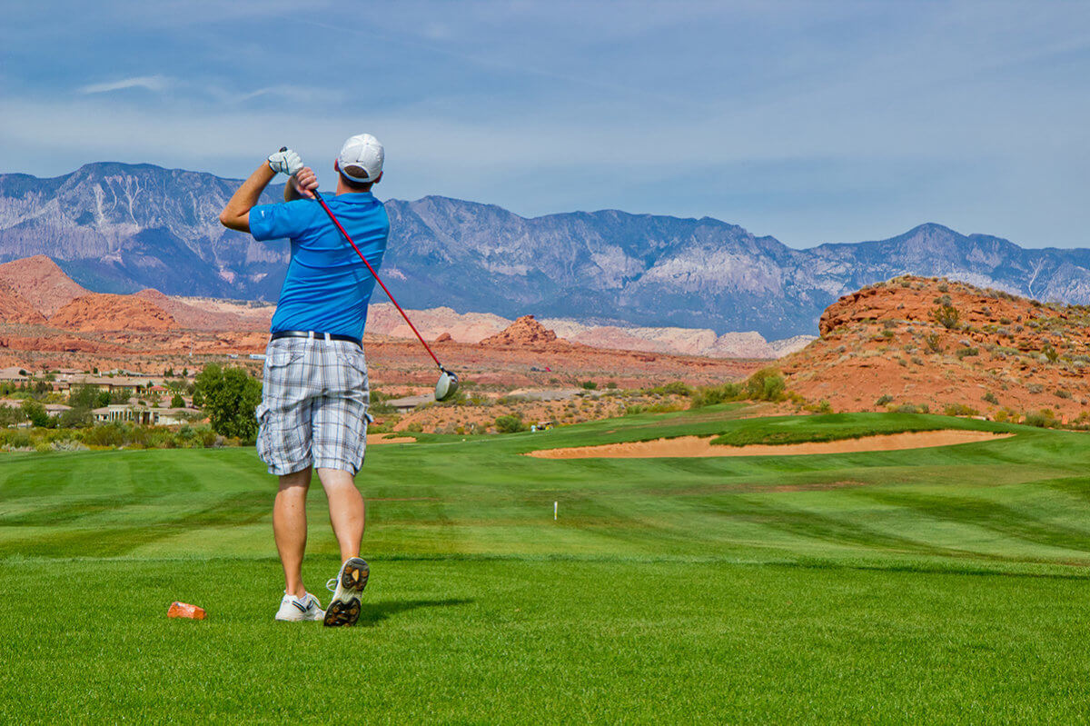 Male golfer in backswing with purple mountain in distance