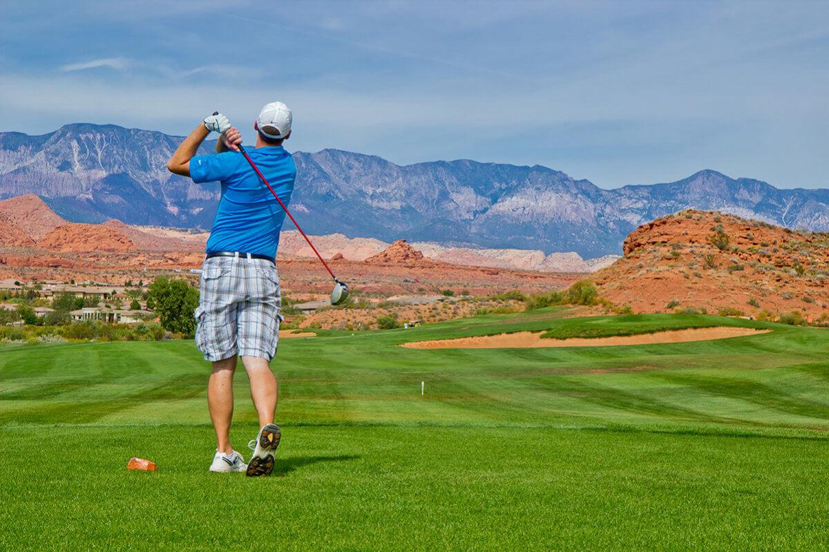 Male golfer in backswing with purple mountain in distance