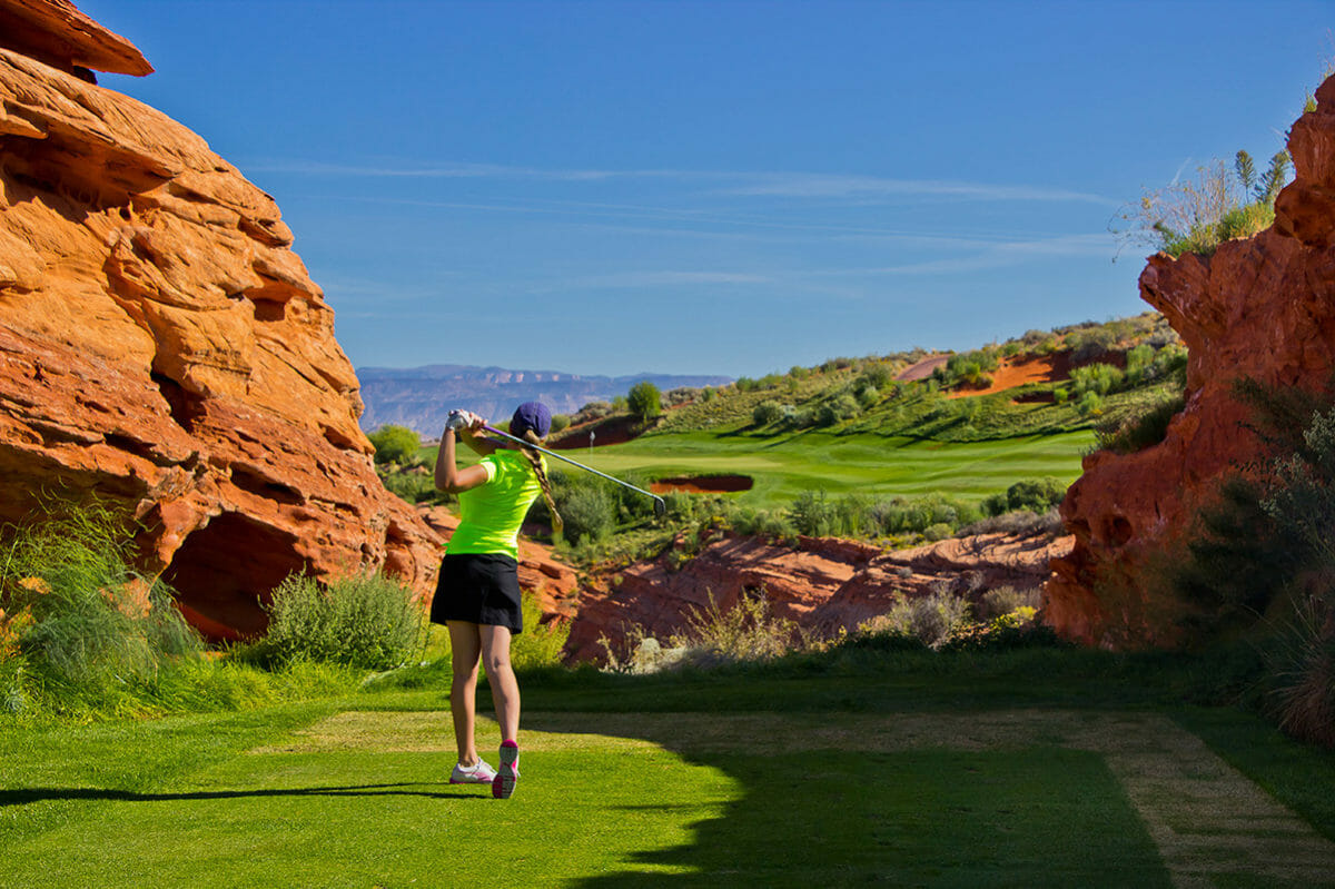 Female golfer midwing between red rock formation under a blue sky.