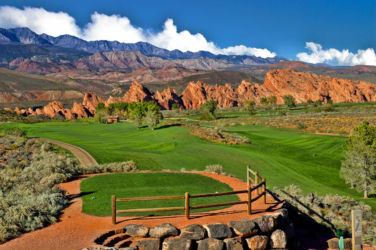 Scenic view of golf course with sharp, red rock jutting towards a blue sky.