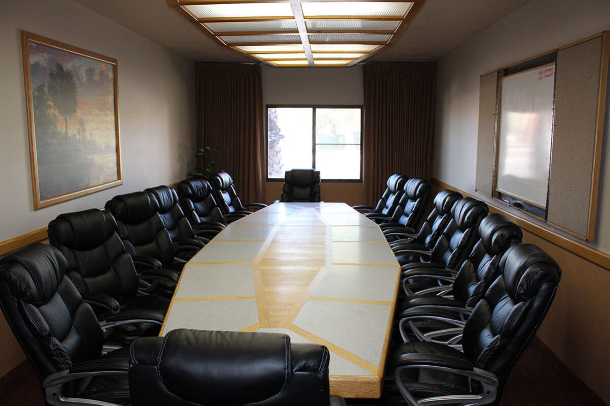 Long table with black leather chairs in hotel board room