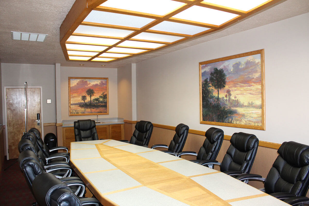 Hotel board room with black leather chairs around long wooden table