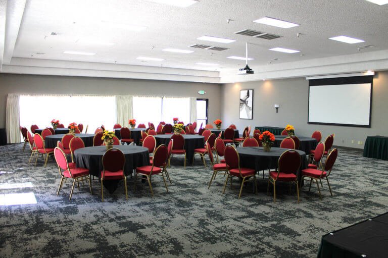 Conference room setting in hotel with black linens and red cloth chairs