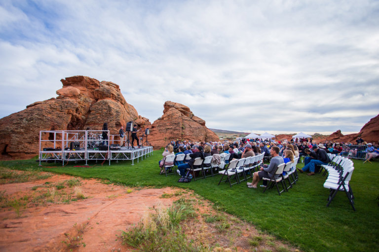Small, outdoor concert with grass and red rocks