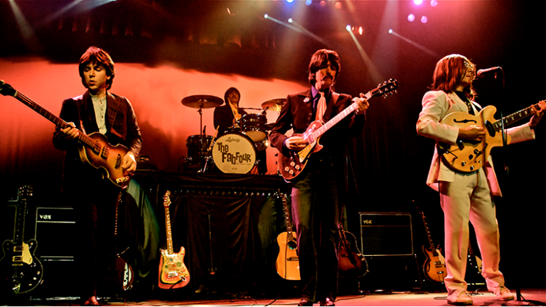 Band named The Fab Four playing on stage