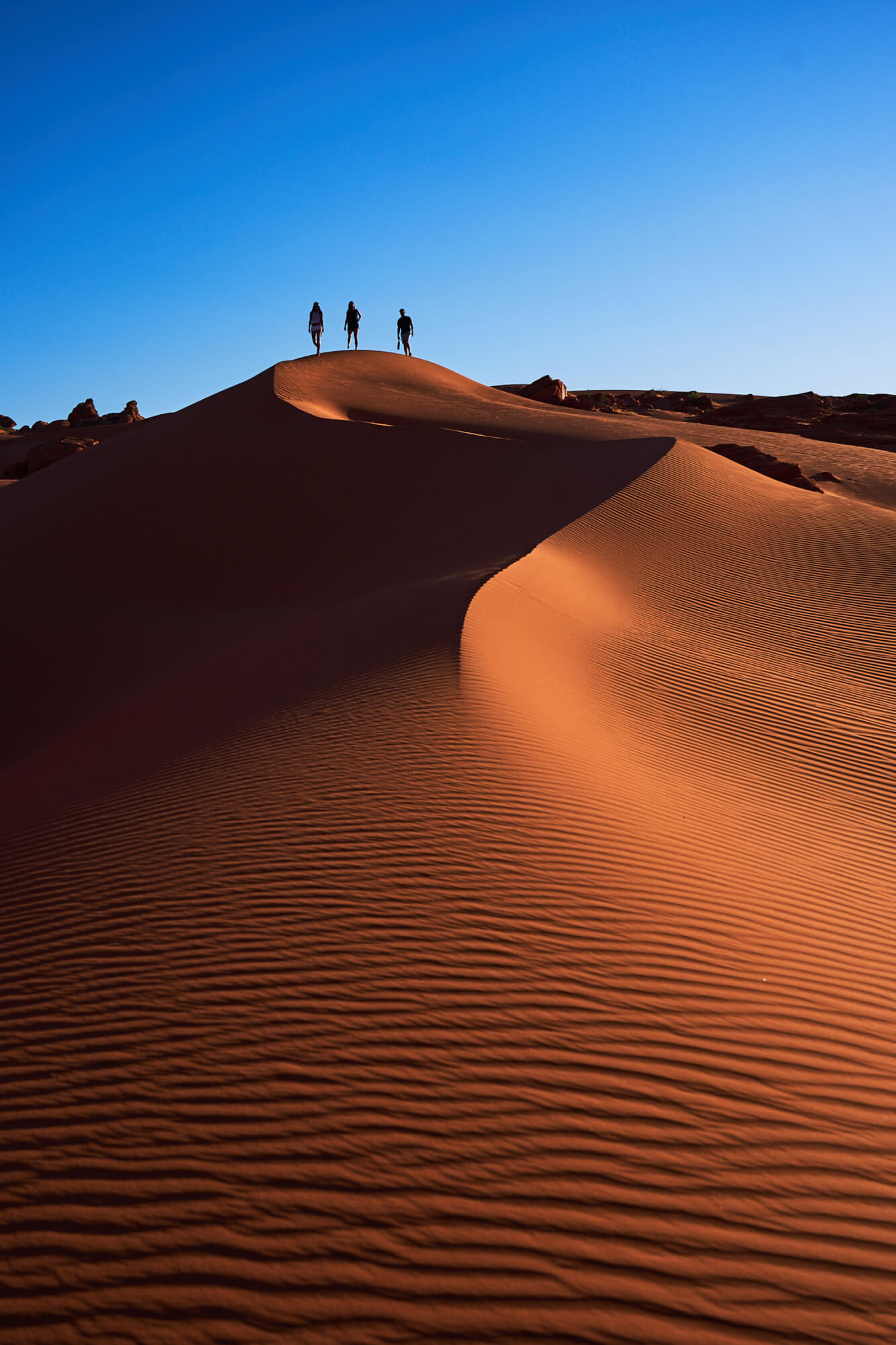 A man and two women walking atop sand dunes