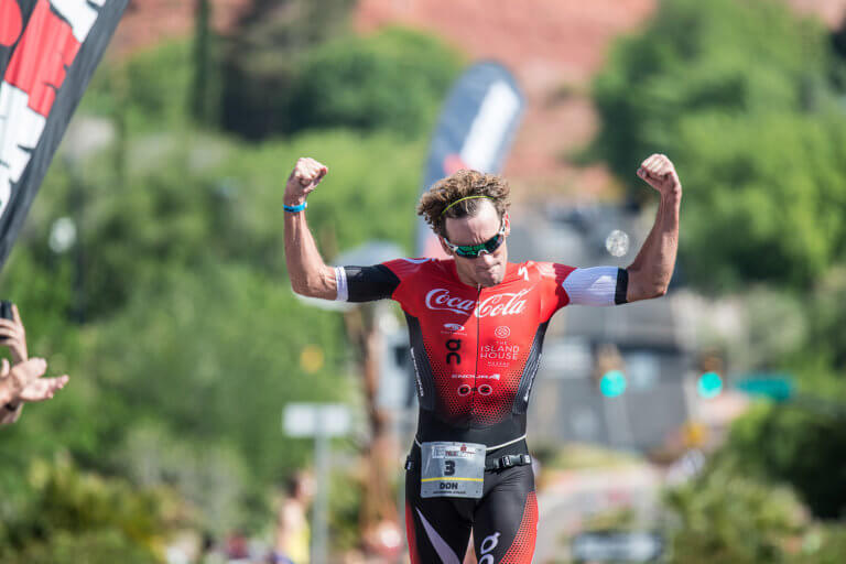 Triathlete running with hands up showing biceps