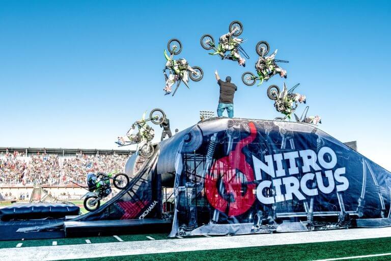 Motocross rider doing back flip over ramp