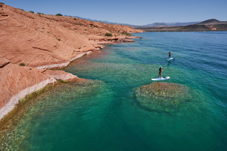 Couple paddleboarding on teal water with red rock formations
