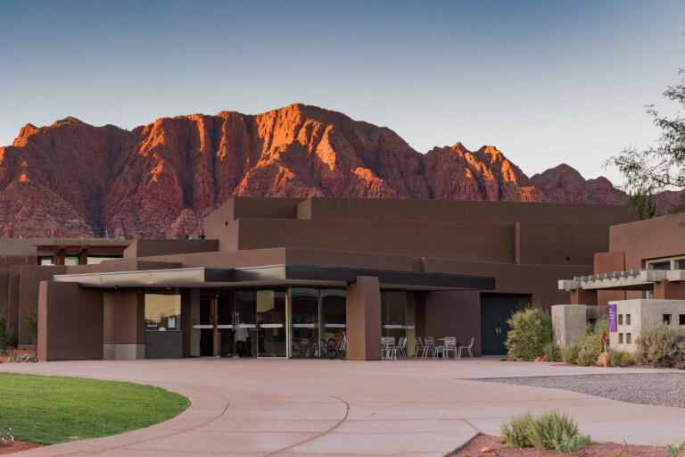 Modern building with red mountains in background