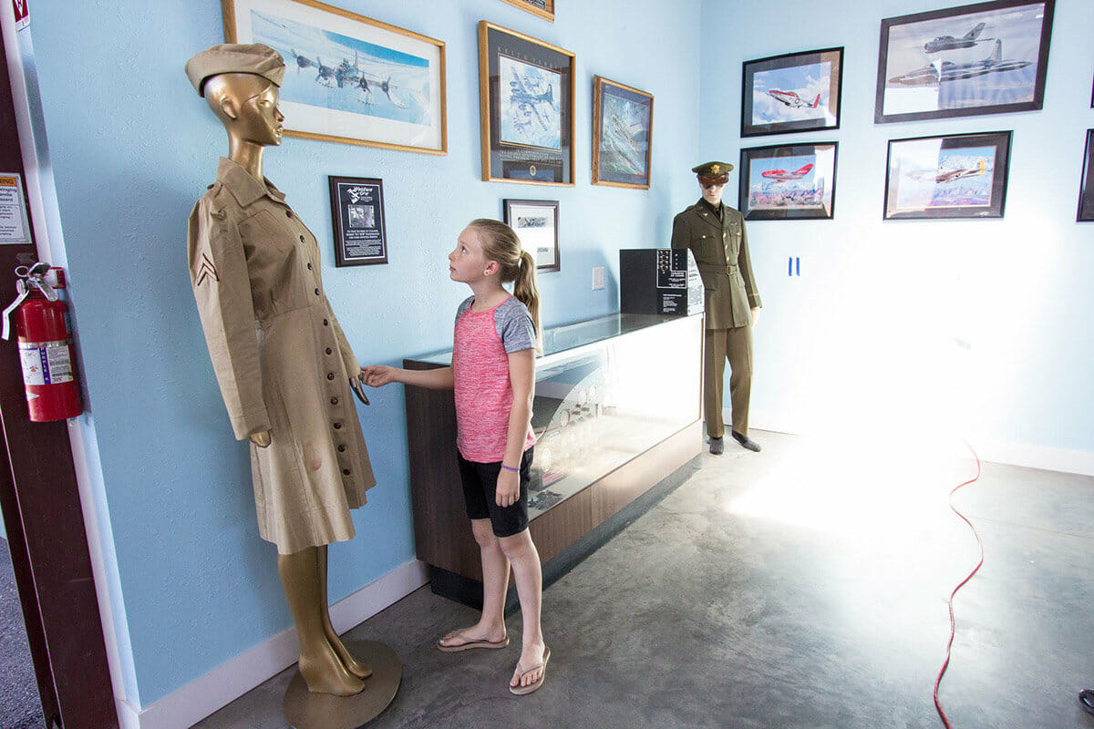 Young girl admiring historic aviation uniforms