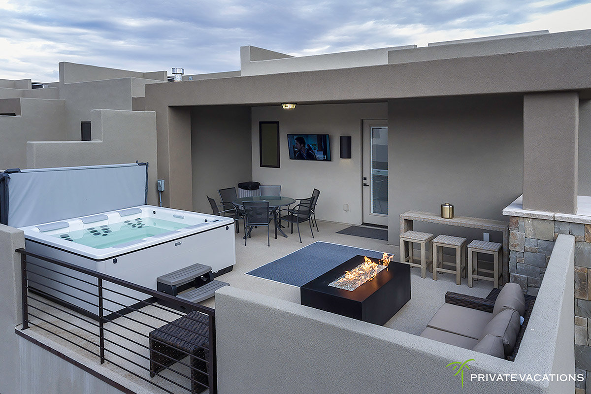 Outdoor patio with jacuzzi, firepit, seating, and TV
