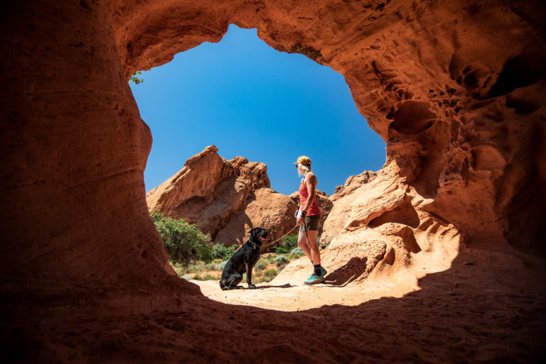 Woman with dog hiking under red sandstone arch