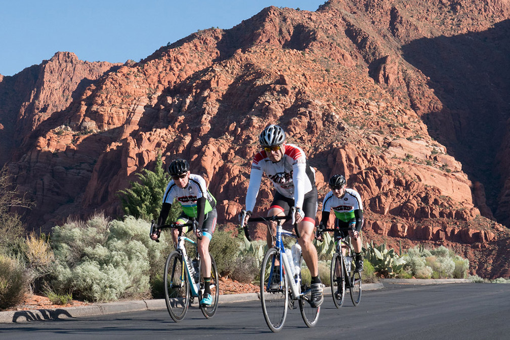 Trio of cyclists in front of red mountains