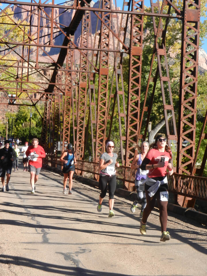 Group of marathon runners on rusted bridge
