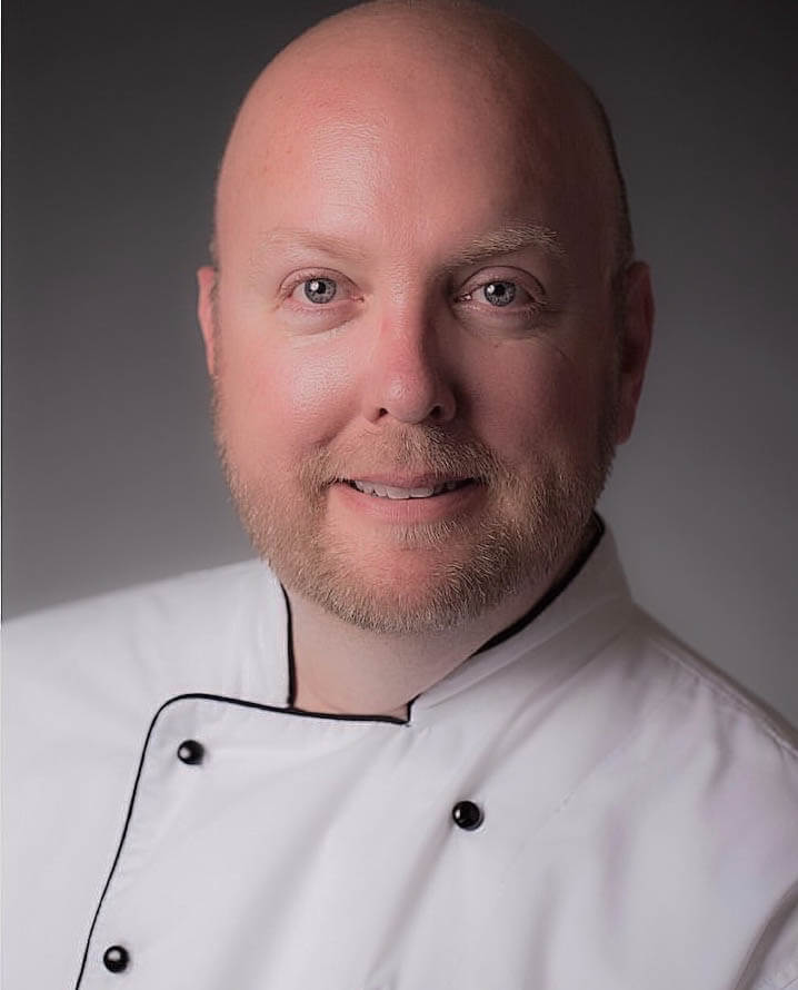 Headshot of white man in chef shirt with beard and bald head