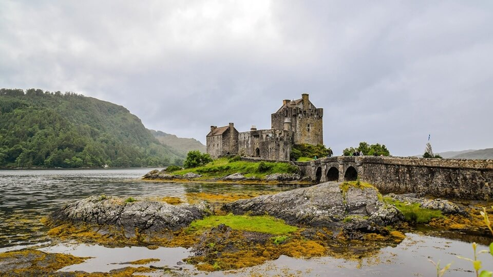 Ancient stone castle with bridge surrounded by water