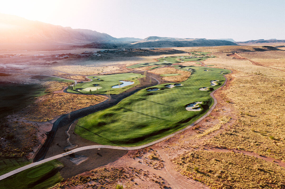 Aerial view of desert golf course with lens flare at sunrise
