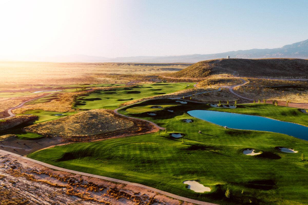 Aerial view ng golf course na may lawa sa pagsikat ng araw