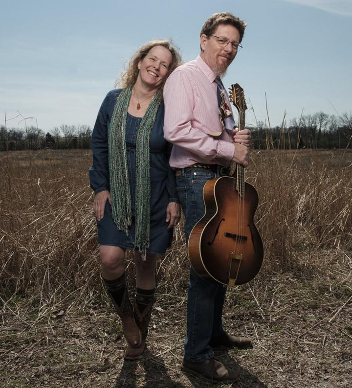 Tim and Jan standing in a field, holding a guitar