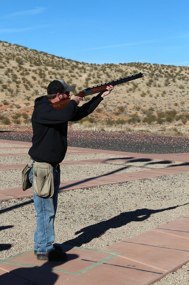 Man in hoodie shooting a shotgun