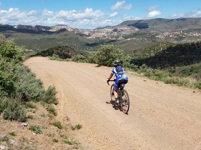 person riding mountain bike on dirt road