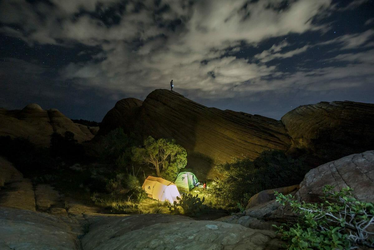 To glødende telt omgitt av fjellformasjoner