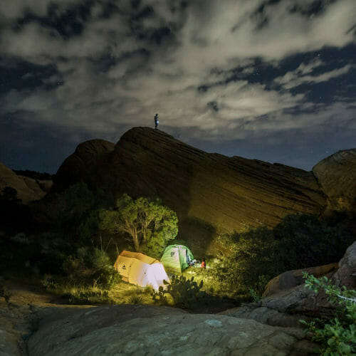 Two glowing tents surrounded by rock formations